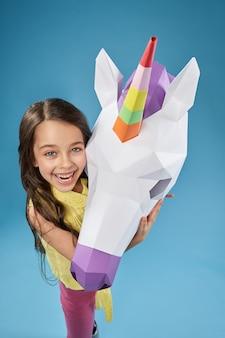Kreatives porträt des kindes mit weißem 3d-einhornkopf.