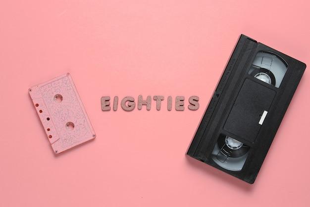 Kreatives retro-stilkonzept, 80er jahre. audio- und videokassette auf rosa mit dem wort achtziger aus holzbuchstaben