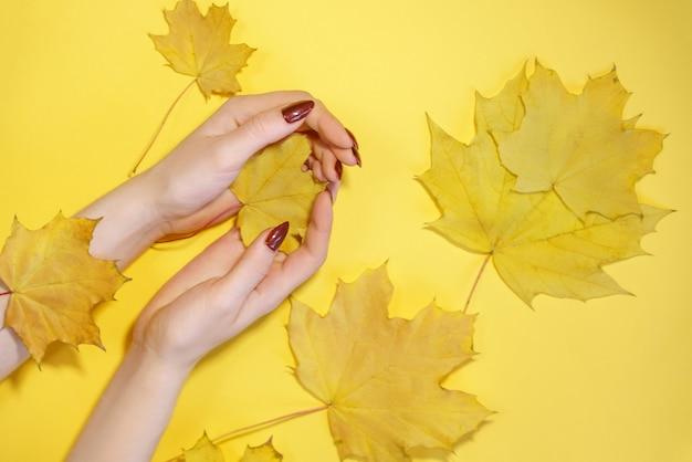 Kreatives schönheitsfoto übergibt gelben hintergrund der mädchen mit farbigen schatten. hautpflege.