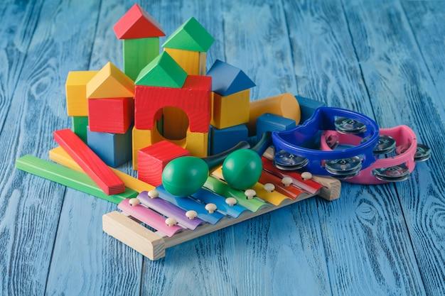 Kreatives spielzeug für kinder. musikinstrumente auf hölzerner blauer oberfläche
