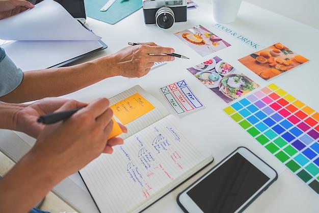 Kreatives startteam des asiatischen werbungsdesigners, das ideen im büro bespricht.