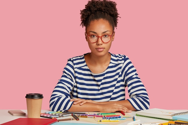 Kreatives studentenmädchen, das am schreibtisch gegen die rosa wand aufwirft