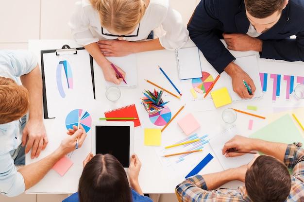 Kreatives team bei der arbeit. blick von oben auf geschäftsleute in smarter freizeitkleidung, die beim sitzen am tisch zusammenarbeiten