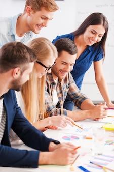 Kreatives team bei der arbeit. seitenansicht von fünf fröhlichen geschäftsleuten in eleganter freizeitkleidung, die beim betrachten der grafiken und diagramme über etwas diskutieren