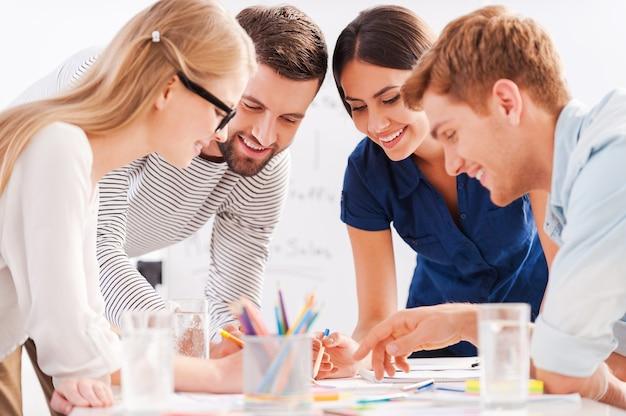 Kreatives team bei der arbeit. vier fröhliche geschäftsleute in eleganter freizeitkleidung diskutieren etwas, während sie sich am tisch lehnen