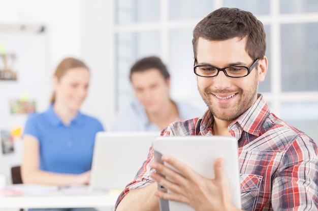 Kreatives team. fröhlicher junger mann mit brille, der ein digitales tablet verwendet und lächelt, während seine kollegen am hintergrund arbeiten