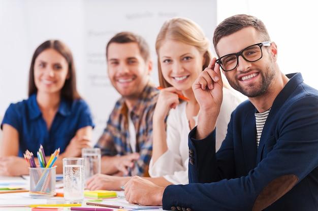 Kreatives team. gruppe selbstbewusster geschäftsleute in eleganter freizeitkleidung, die zusammen am tisch sitzen und lächeln