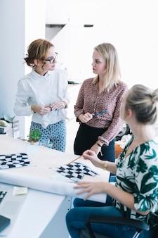 Kreatives team von geschäftsfrauen, die karierte flagge im büro vorbereiten