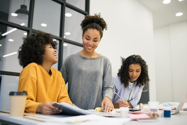 Kreatives team von lächelnden lockigen afroamerikanischen frauen, die neues startprojekt am arbeitsplatz planen. brainstorming. studenten lernen modedesign im atelier. junge hipster arbeiten zusammen