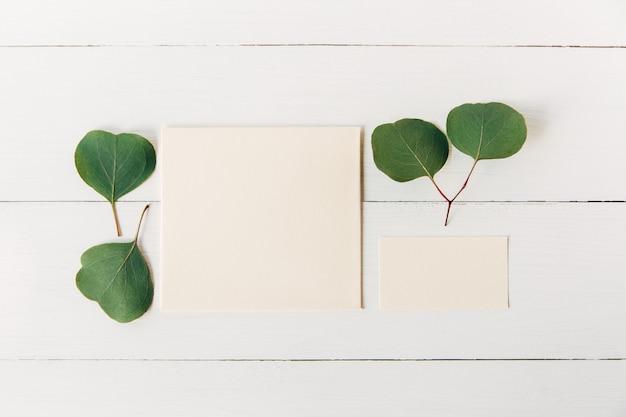 Kreatives und stilvolles modell mit grünen blättern leerer umschlag und visitenkarte