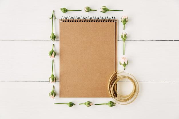 Kreatives und stilvolles modell mit grünen blättern und rosa rosenblankes braunes notizbuch