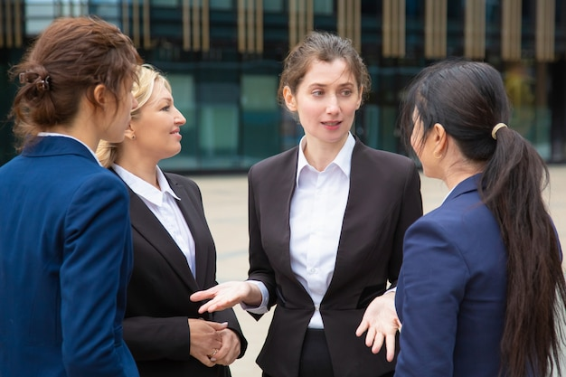 Kreatives weibliches geschäftsteam, das projekt im freien bespricht. geschäftsfrauen tragen anzüge, die zusammen in der stadt stehen und sprechen.
