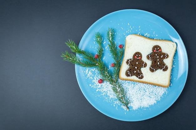 Kreatives weihnachtsfrühstück auf einem blauen teller auf schwarz