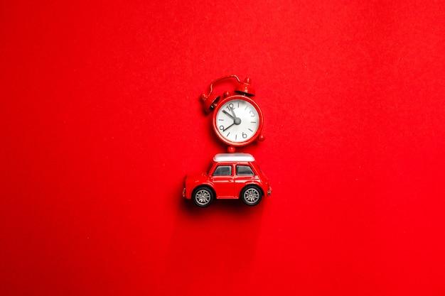 Kreatives weihnachtskonzept des runden uhr- und spielzeugautomodells des roten weckers auf rotem hintergrund, draufsicht. minimale kreative ferien- und reisekonzepte.
