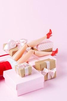 Kreatives weihnachtslayout mit puppenbeinen und geschenkboxen auf pink