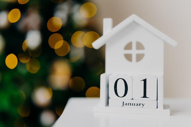 Kreatives weißes haus mit schriftlichem datum und weihnachtsbaum mit lichtern. erster januar. frohes neues konzept