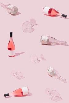 Kreatives winkelmuster aus leeren und vollen roséweinflaschen und kristallgläsern. pastellrosa hintergrund. erfrischendes alkoholisches sommergetränkkonzept.