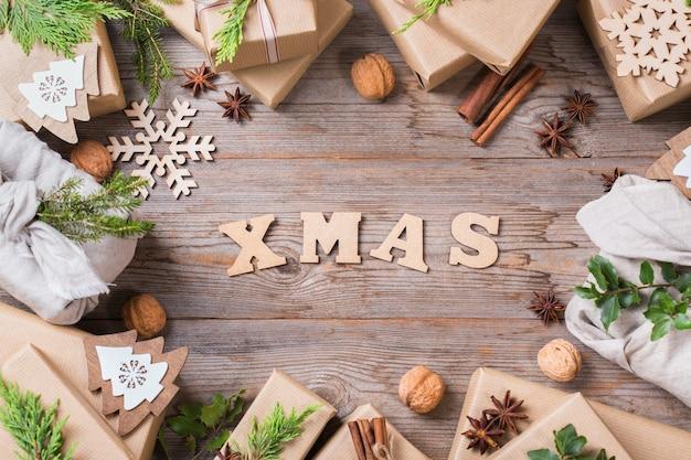 Kreatives zero-waste-weihnachtskonzept. geschenkboxen mit handgemachtem, umweltfreundlichem bastelpapier und traditioneller furoshiki-stoffverpackung im japanischen stil. flacher laienhintergrund der hölzernen draufsicht