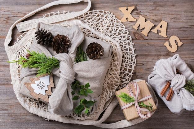 Kreatives zero-waste-weihnachtskonzept. geschenkboxen mit handgemachtem, umweltfreundlichem bastelpapier und traditioneller furoshiki-stoffverpackung im japanischen stil in einem netzbeutel. draufsichthintergrund flach legen