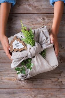 Kreatives zero-waste-weihnachtskonzept. hände, die handgemachte geschenkboxverpackungen in umweltfreundlichem furoshiki-stoff im traditionellen japanischen stil geben