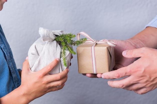 Kreatives zero-waste-weihnachtskonzept. menschen tauschen handgemachte geschenkboxen aus, die in umweltfreundlichem kraftpapier und traditionellem furoshiki-stoff im japanischen stil verpackt sind. familienzeit, festliche vorbereitung.