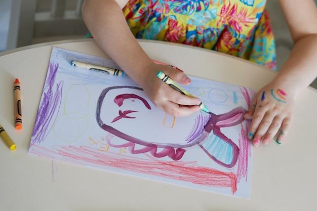 Kreativität der kinder. kleines kindermädchen zeichnet mit wachsstiften zu hause. das konzept des online-fernunterrichts für die zeit der globalen quarantäne.