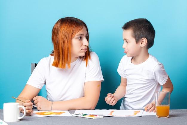 Kreativität der kinder. mutter und kind sohn malen aquarell hausaufgaben für kindergarten auf blauem hintergrund