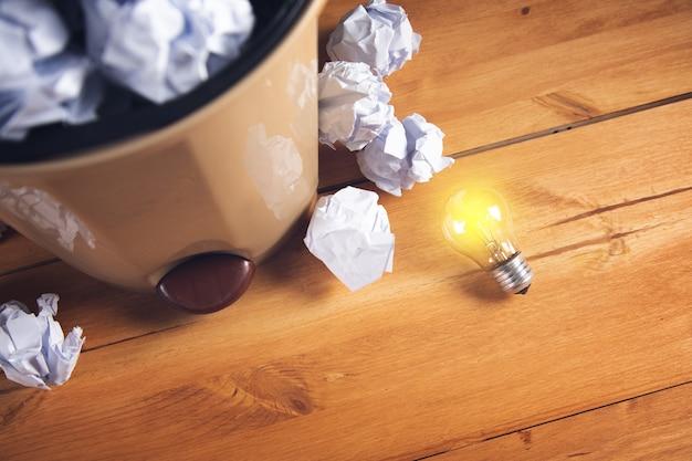 Kreativität geschäftsideen konzept mit glühbirne mit papierkorb papierkugeln recyceln