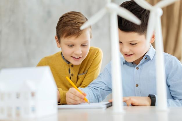 Kreativität schwingt. angenehme jugendliche jungen, die das büro ihres vaters besuchen und in das notizbuch zeichnen, während sie auf ihn warten