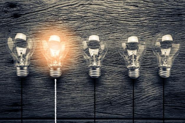 Kreativitätsideen mit glühlampe auf hölzernem beschaffenheitshintergrund