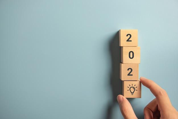 Kreativitätsinspirationskonzepte, frauenhand, die hölzernen block mit neuem jahr 2020 und glühlampenikone, planungsideen vereinbart.