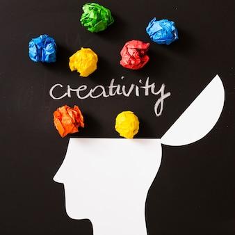 Kreativitätstext mit buntem zerknittertem papierball über dem offenen kopf gegen schwarzen hintergrund