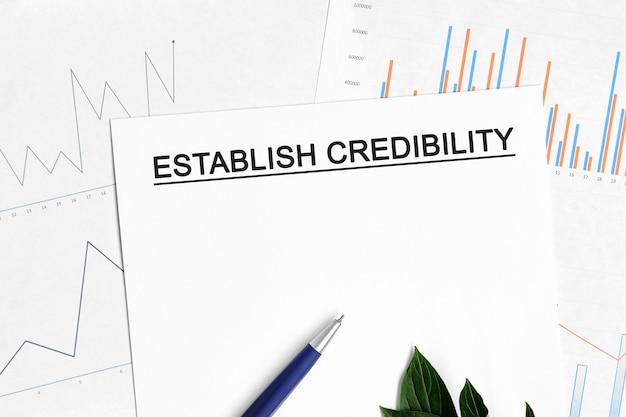Kredibilitätsdokument mit grafiken, diagrammen und blauem stift einrichten.