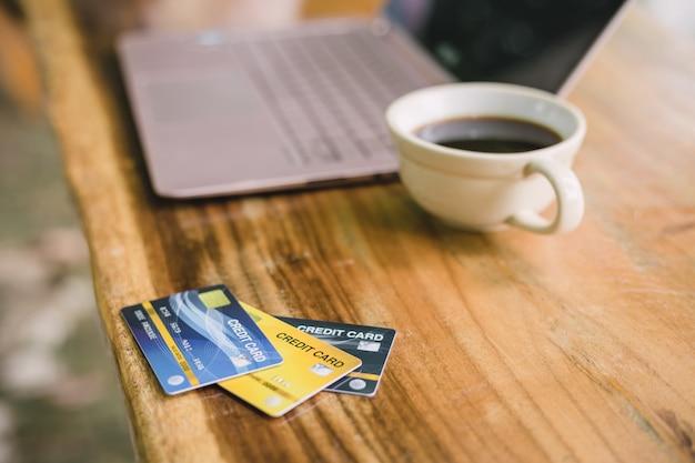 Kreditkarte auf laptop mit dem kaffee, im freien