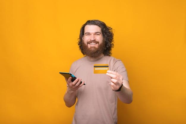 Kreditkarte für online-shopping, schöner bärtiger hipster-mann, der karte zeigt und tablette verwendet
