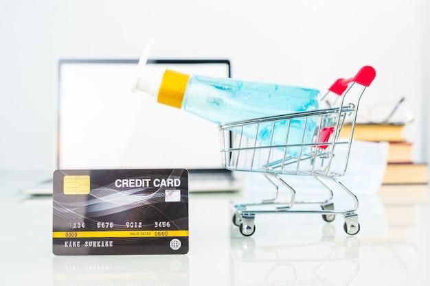 Kreditkarte im einkaufswagen vor laptop-bildschirm mit alkohol-gel-flasche, work from home-konzept