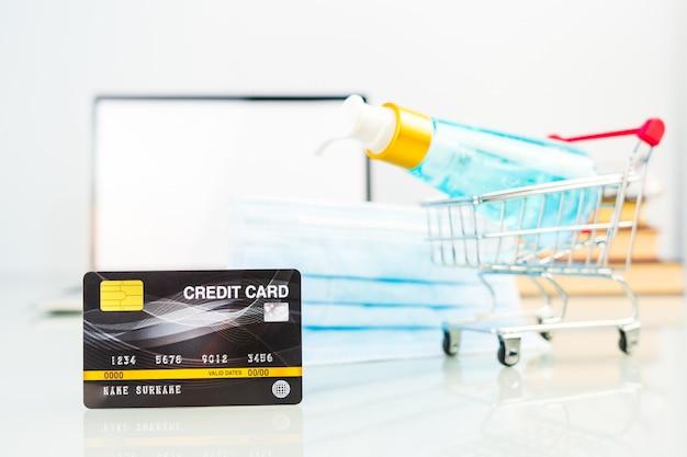 Kreditkarte im einkaufswagen vor laptop-bildschirm mit alkohol-gel-flasche