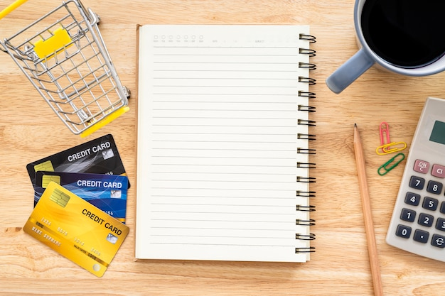 Kreditkarte im warenkorb mit notizbuch, einem bleistift, blumentopfbaum, taschenrechner auf hölzernem hintergrund, draufsicht des online-bankings mit bürotisch.