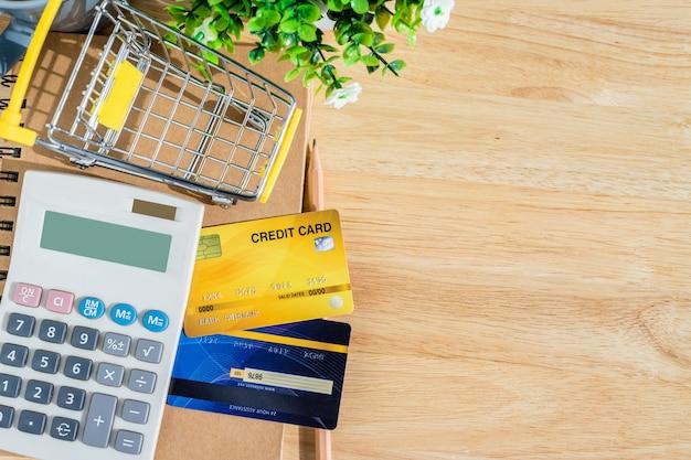 Kreditkarte im warenkorb mit notizbuch und taschenrechner