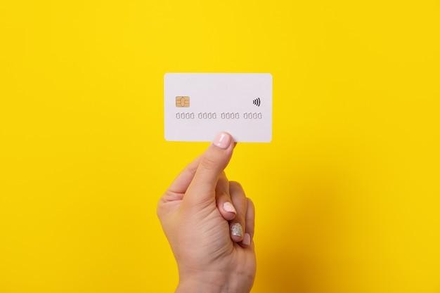 Kreditkarte in der hand, karte mit elektronischem chip über gelbem hintergrund