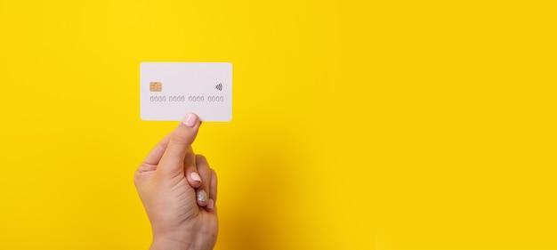 Kreditkarte in der hand über gelbem hintergrund, panoramabild