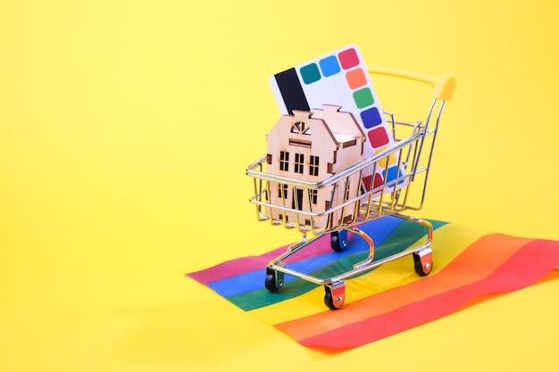 Kreditkarte, kleines haus in einem einkaufswagen auf der flagge der lgbt gemeinschaft, gelber hintergrund, kopierplatz