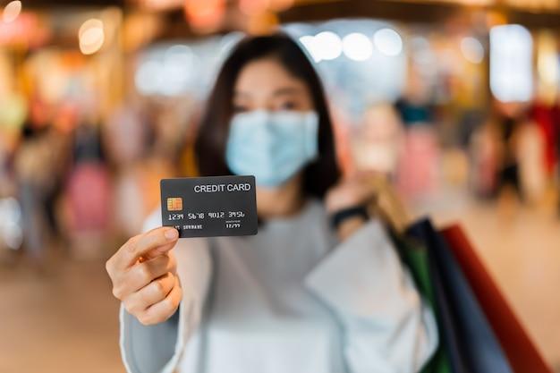 Kreditkarte mit frau, die medizinische maske im einkaufszentrum zur verhinderung von coronavirus trägt