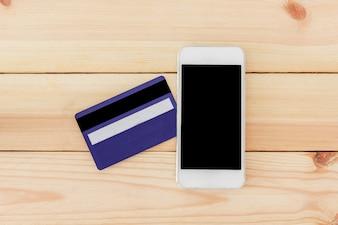 Kreditkarte mit Smartphone auf Tabelle, Draufsicht mit Kopienraum. Online-Shopping-Konzept