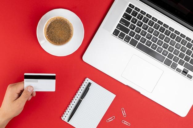Kreditkarte neben kaffee und notebook verspotten