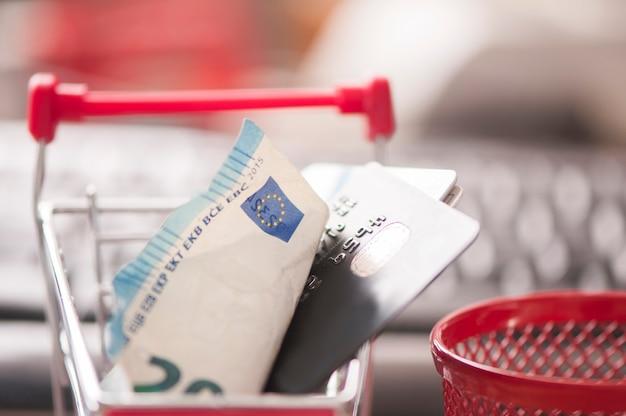 Kreditkarte und geld im warenkorb