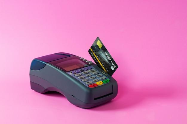 Kreditkarte und kreditkartenscanner auf einem rosa hintergrund
