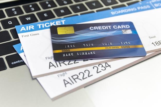 Kreditkarte und pässe in der nähe von laptop auf tisch. online-ticketbuchungskonzept