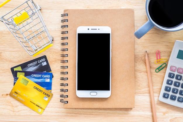 Kreditkarten mit notebook und taschenrechner auf einem desktop