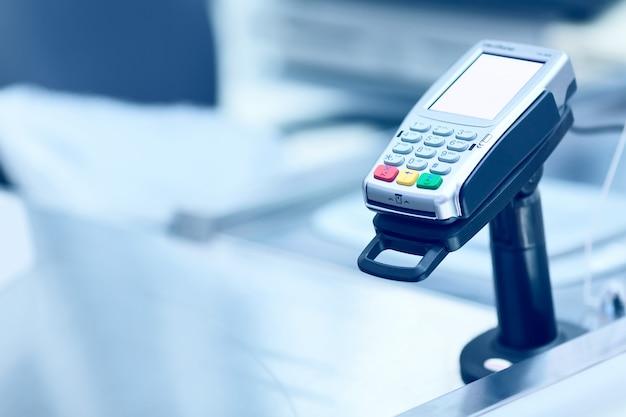 Kreditkarten-pos-terminal an der kasse in einem geschäft.